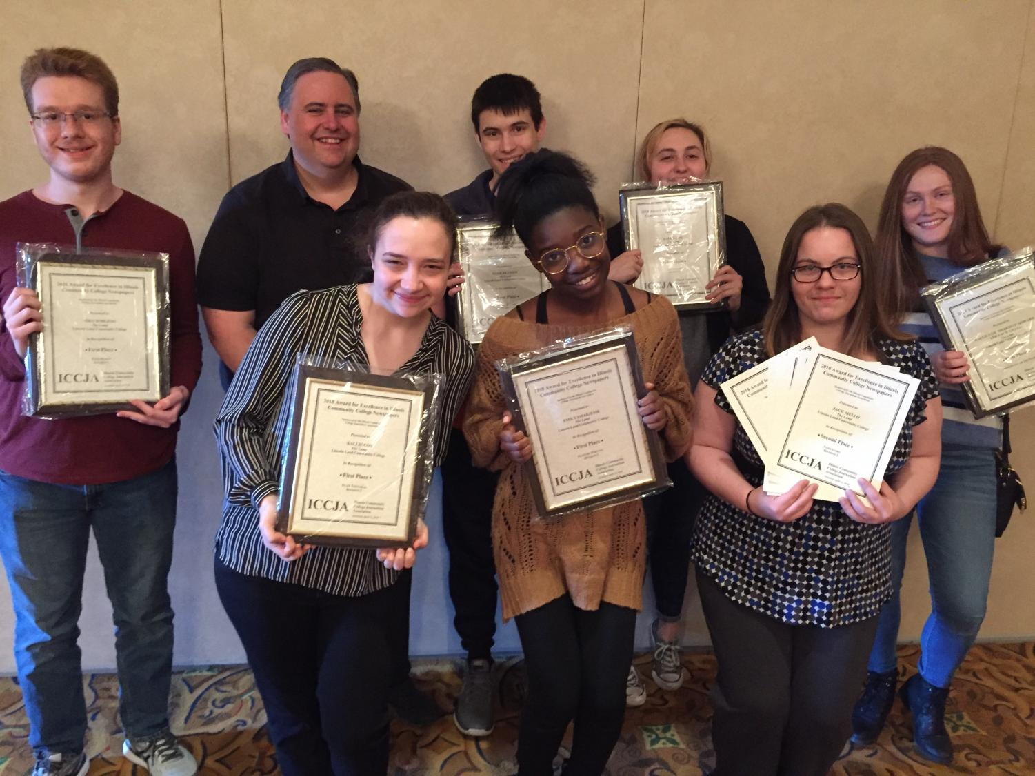 Lamp staff hold up the 19 awards that the staff won at the Illinois Community College Journalism Association's spring conference on Friday, April 12, 2019, in Utica, Illinois. In the front row are Tess Peterson; Regina Ivy, assistant editor; and Rosanna Cravens. Back row are Tyler Buske, assistant editor; Tim McKenzie, adviser, Ryan Scott; Sage Gass; and Meredith Howard, editor-in-chief.