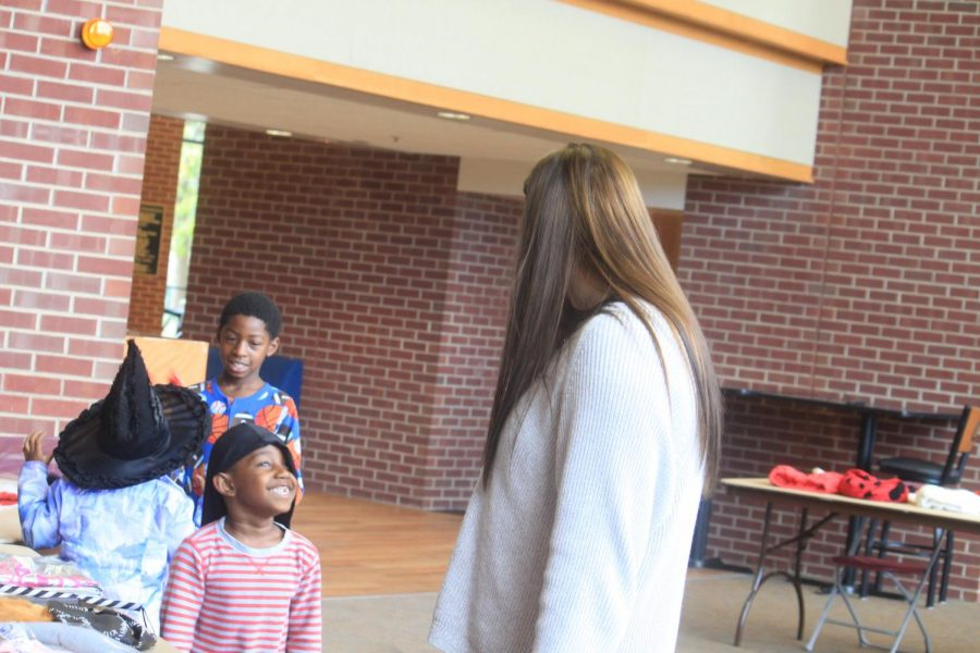 Honors Club President Jordan Bruder searches for costumes with kids.